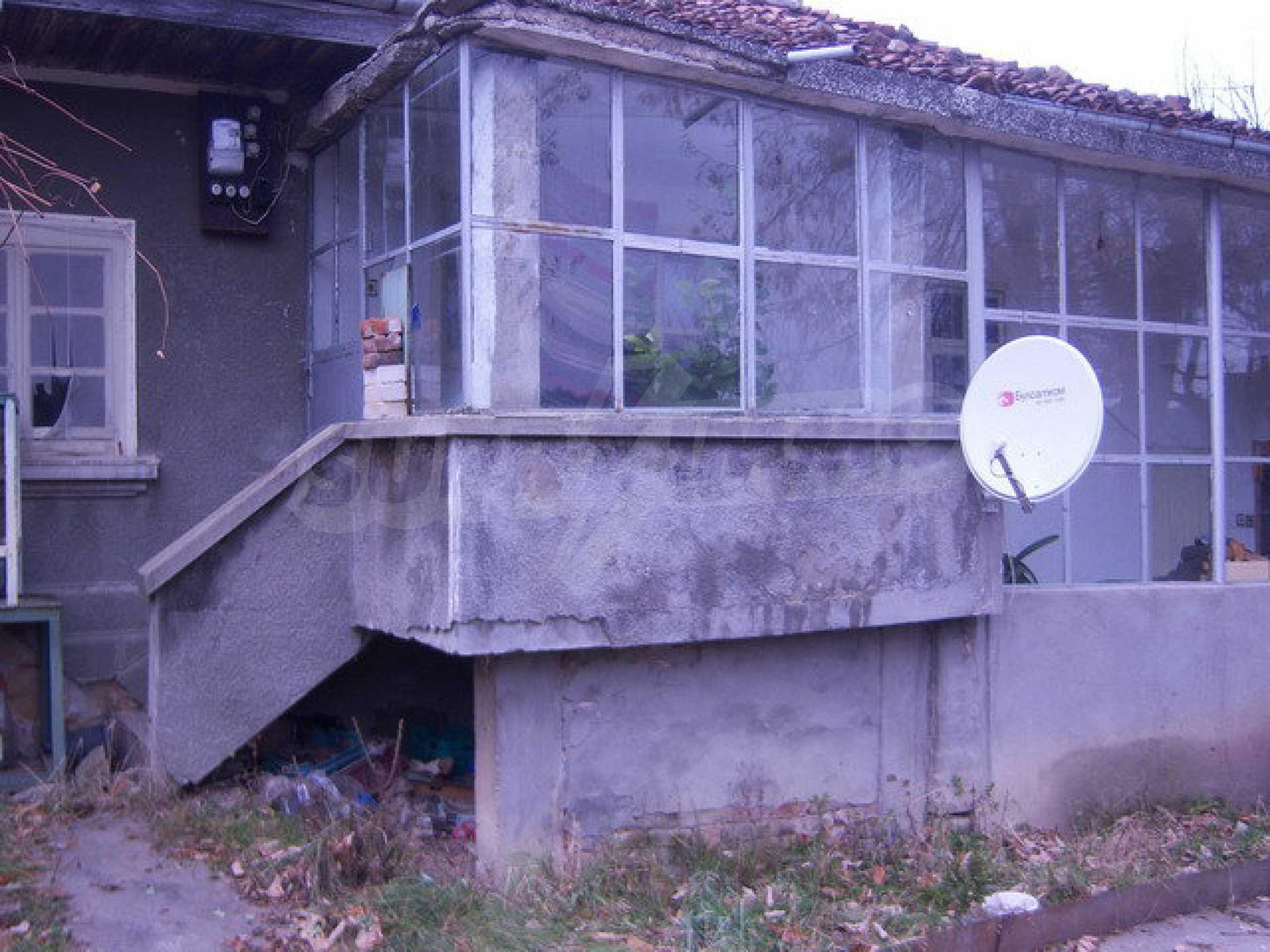 Одноэтажный дом около леса и у подножия гор.