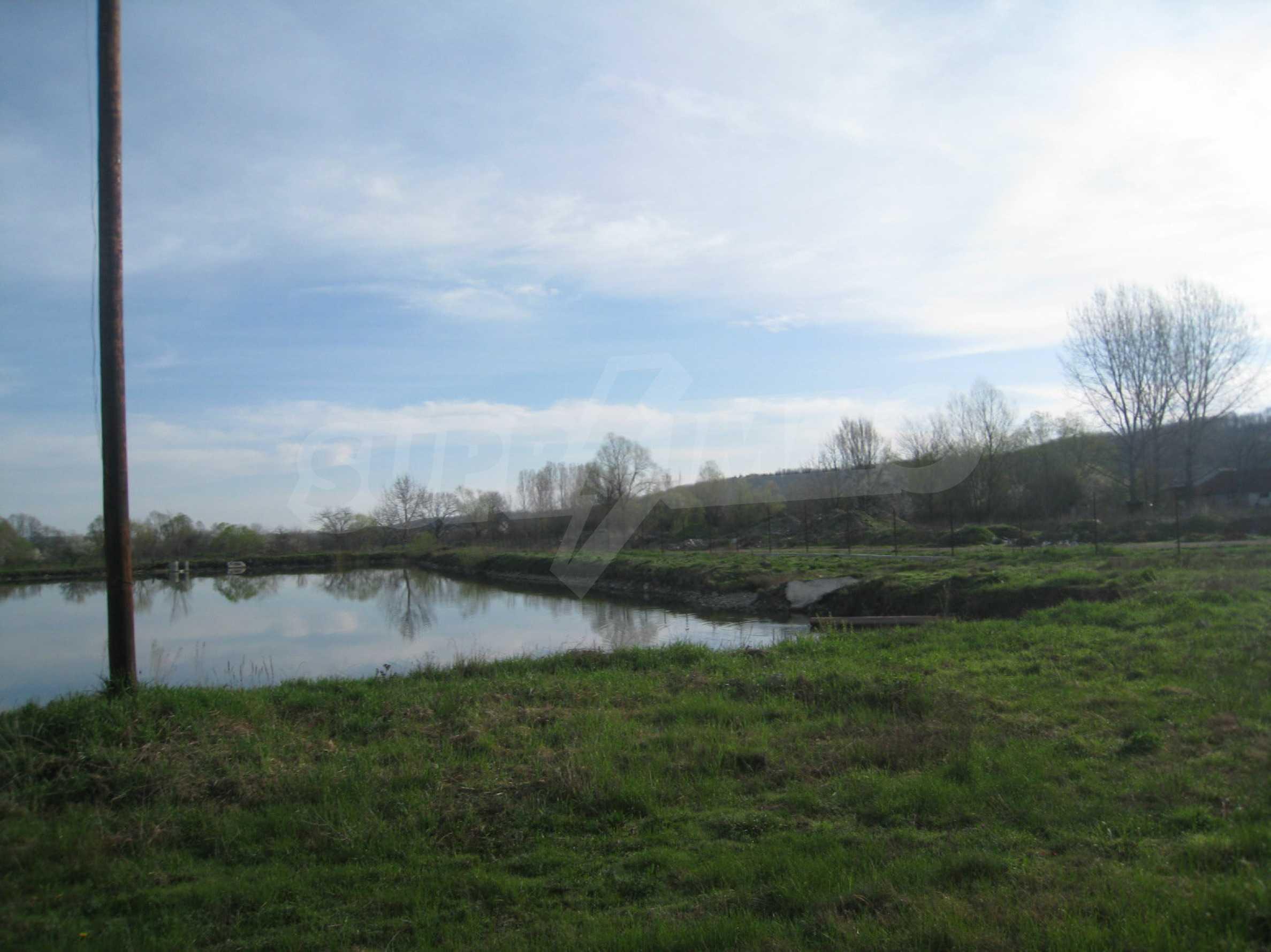 Fishpond, warehouses, residential areas and asphalt ground near Montana 21